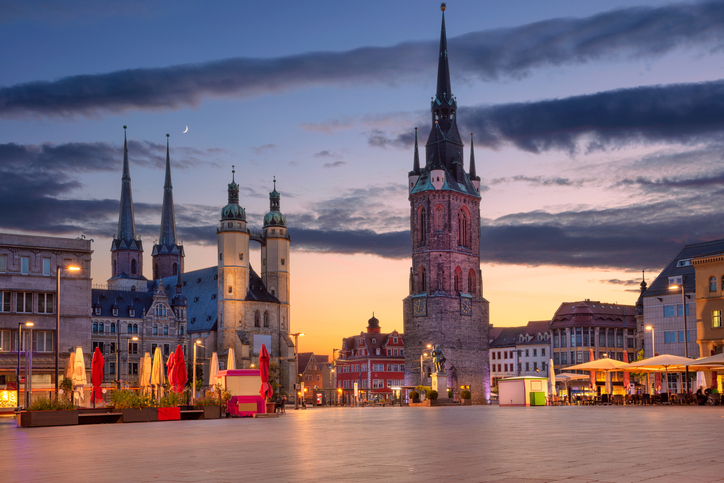 Cityscape image of historical downtown of Halle (Saale) with the Red Tower and the Market Place during dramatic sunset.